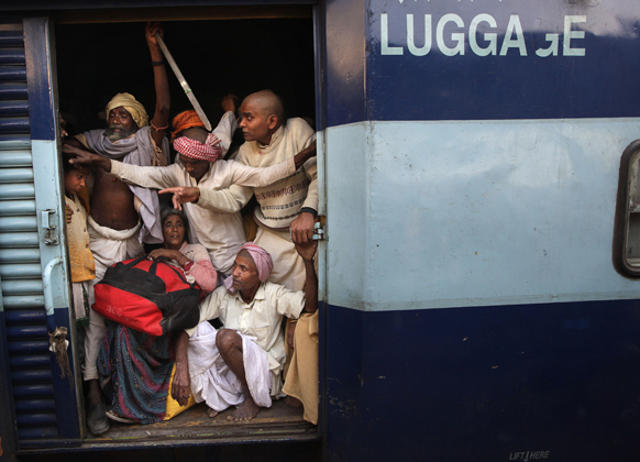 महाकुंभ में स्नान करने के बाद इलाहाबाद रेलवे स्टेशन पर एक ट्रेन के माल ढोने वाले डिब्बे में सवार लोग।
