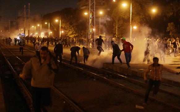 काहिरा में राष्ट्रभवन के पास उपद्रवियों को खदेड़ती पुलिस।