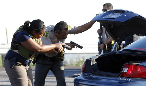 अमेरिका के लॉस एंजिल्स में सुरक्षा जांच में जुटे पुलिसकर्मी।
