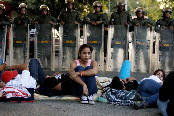 क्यूबा के दूतावास के बाहर सड़क के किनारे जमे ये छात्र-छात्राएं वेनेजुएला के काराकस में भर्ती वेनेजुएला के राष्ट्रपति ह्यूगो शावेज की सेहत के बारे जानना चाह रहे हैं।