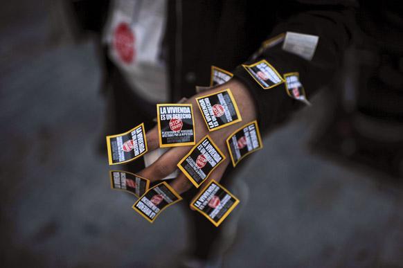 नॉर्थ स्पेन में हाथ पर स्टिकर चिपकार पर्दशन करते प्रदर्शनकारी।