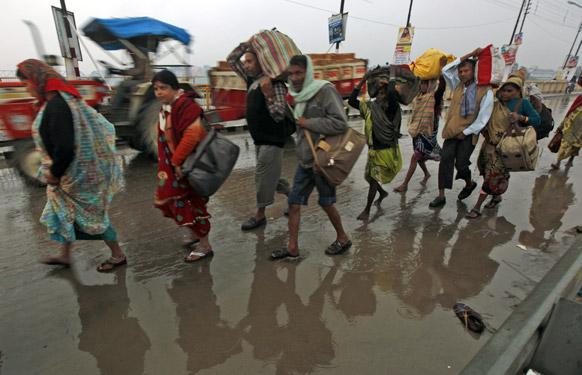 इलाहाबाद के संगम में महाकुंभ मेले के दौरान पवित्र स्नान के लिए बारिश में भींग कर जाते श्रद्धालु।