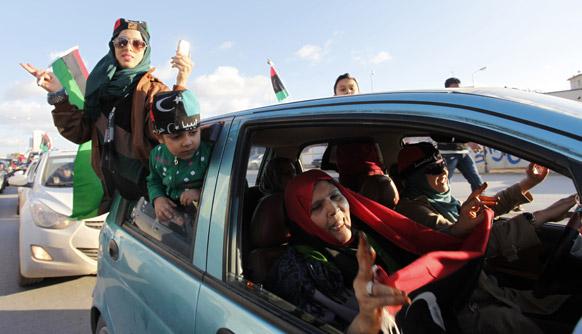 लीबिया में मोअम्मर गद्दाफी के शासन के खात्मे के लिए हुई बगावत के दो साल पूरे होने पर तहरीर चौक पर जश्न मनाते लोग।