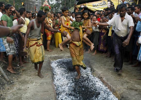 यंगून में एक धार्मिक आयोजन के दौरान दो बच्चियों के साथ जलते अंगारों को पार करता एक व्यक्ति।