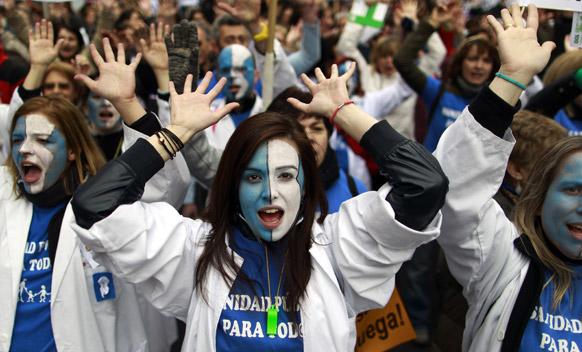 मेड्रिड में कटौती उपायों को लेकर प्रादेशिक सरकार के खिलाफ विरोध- प्रदर्शन करते लोग।