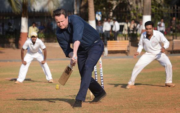 भारत दौरे पर आए ब्रिटेन के प्रधानमंत्री डेविड कैमरन मुंबई में बच्चों के साथ क्रिकेट खेलते हुए।