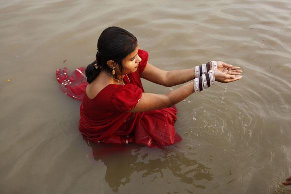 इलाहाबाद के संगम तट पर चल रहे महाकुंभ मेले के दौरान गंगा की पूजा अर्चना करती एक महिला श्रद्धालु।
