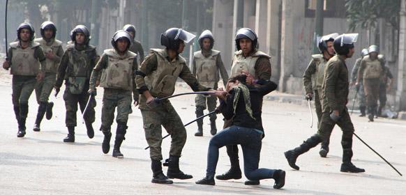 मिस्र की राजधानी काहिरा में तहरीर चौक पर सेना पुलिस से संघर्ष के दौरान एक महिला प्रदर्शनकारी को गिरफ्तार करते मिस्र सेना के जवान।