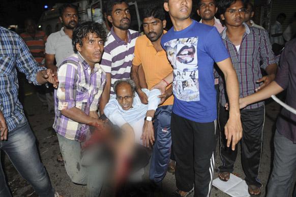 हैदराबाद में धमाकों के बाद विस्फोट में घायल एक व्यक्ति को राहत पहुंचाने की कोशिश करते हुए लोग।