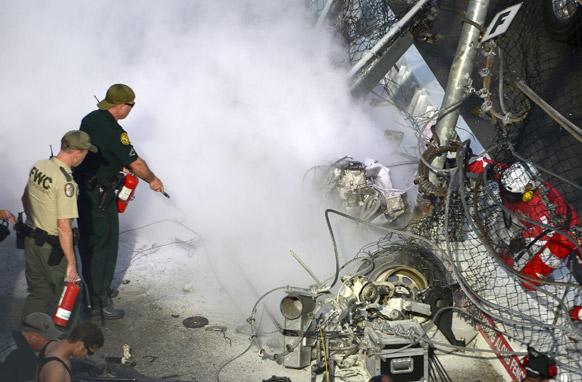 फ्ला में ऑटो रेस के दौरान ड्राइवर काइल लार्जन की कार में लगी आग को बुझाते आपात अधिकारी।