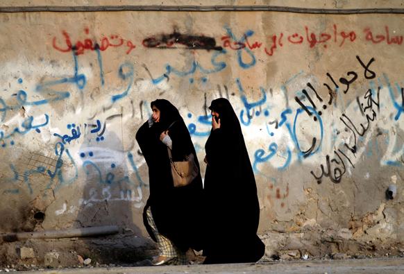 बहरीन में सरकार विरोधी प्रदर्शनकारी और दंगा नियंत्रक पुलिसकर्मी के बीच संघर्ष के दौरान अश्रु गैस से बचकर निकलती हुई महिलाएं।
