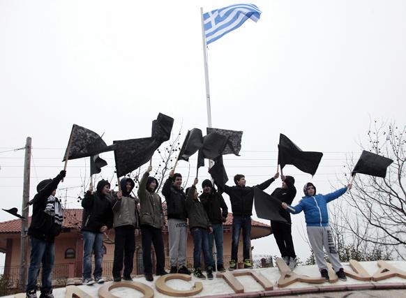 हलकिडीकी ग्रीस में गोल्ड माइन के खिलाफ काले झंडे लेकर विरोध जताते हुए युवा प्रदर्शनकारी।