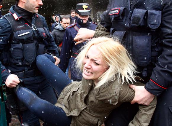 इटली के मिलान में पूर्व प्रधानमंत्री सिल्वियो बर्लुस्कोनी के वोट डालने के दौरान विरोध जताती एक महिला प्रदर्शनकारी को ले जाते हुए पुलिसकर्मी।
