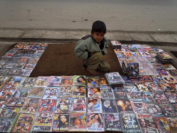आफगानिस्तान के जलालाबाद में सड़क किनारे फिल्मों की सीडी बेचता एक लड़का।