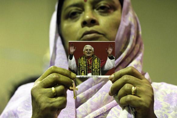 कोलकाता में एक कैथेलिक महिला पोप जॉन बेनेडिक्ट की तस्वीर को दिखाते हुए।