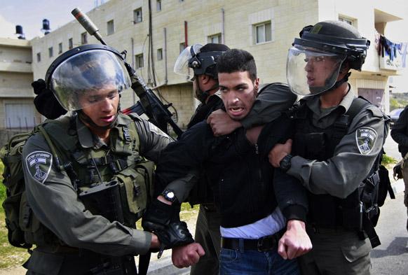 वेस्ट बैंक के समीप एक फलीस्तीनी नागरिक को हिरासत में लेती इजरायली पुलिस।
