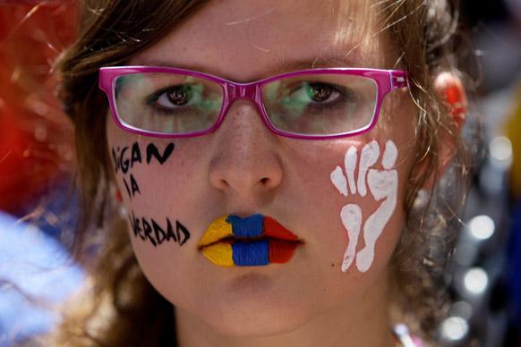 वेनेजुएला के कराकस में प्रदर्शनकारी होंप रंग लगाकर प्रदर्शन करते हुए।