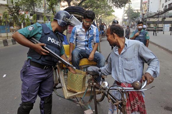 ढाका में देशव्यापी हड़ताल के दौरान पुलिसकर्मी सर्च करते हुए।