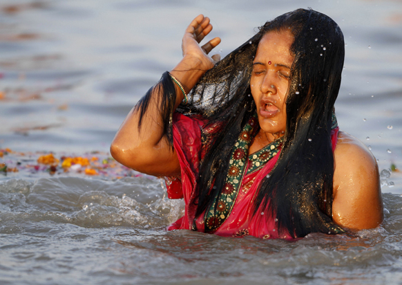 इलाहाबाद: महाकुंभ के दौरान गंगा, यमुना और अदृश्य सरस्वती के संगम तट पर आस्था की डुबकी लगाती हुई एक महिला श्रद्धालु।