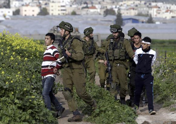 जेनिन में एक विरोध मार्च के दौरान फलस्तीनी युवाओं को गिरफ्तार करते हुए इजरायल के सैनिक।
