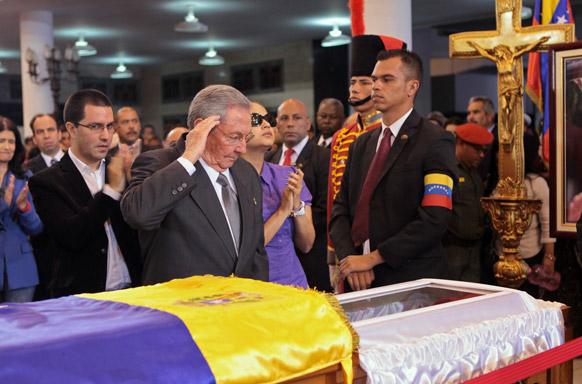 क्यूबा के राष्ट्रपति पोल कास्ट्रो वेनेजुएला के राष्ट्रपति ह्यूगो शावेज के पार्थिव शरीर को सैल्यूट करते हुए।