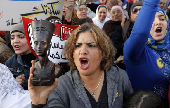 मिस्र के काहिरा में प्रदर्शन के दौरान फारोनिक क्वीन की मूर्ति को लेकर प्रदर्शन करती महिलाएं।