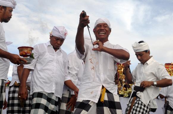 इंडोनेशिया के बाली में हिंदू धार्मिक यात्रा के दौरान बाली का एक नागरिक।