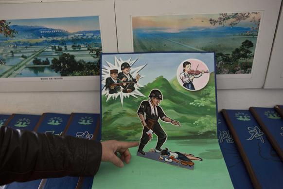 उत्तर कोरिया के प्योंगयांग में एक शिक्षक ने चिल्ड्रेन पॉप अप बुक में यूएस सैनिक द्वारा कोरियन महिला को मारते हुए दिखाया।