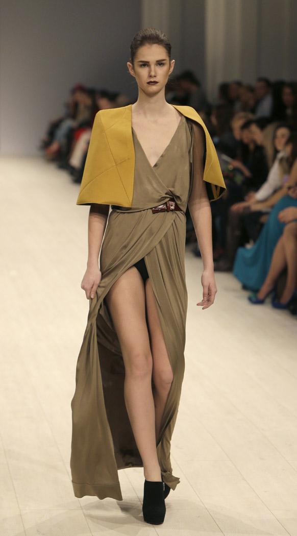 कीव में फैशन वीक के दौरान यूक्रेन के डिजायनर डॉमनॉफ के कपड़ों को पेश करती एक मॉडल।