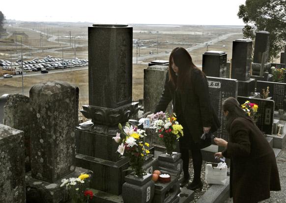 जापान में सुनामी में मारे गए लोगों को श्रद्धांजलि देते परिजन।