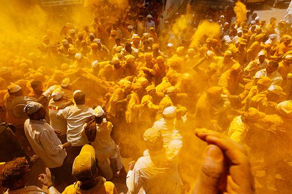 महाराष्ट्र के पुणे में सोमवती अमावस्या के दौरान एक दूसरे पर हल्दी फेंकते लोग।