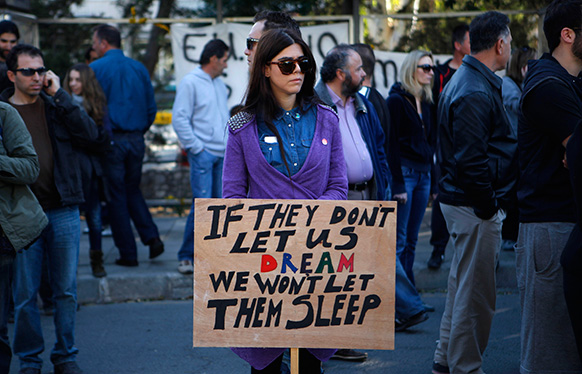 साइप्रस में सरकार की नीतियों के खिलाफ विरोध करती एक महिला।