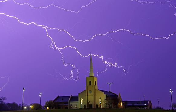 अलबामा के नजदीक एक चर्च के ऊपर आसमान में गरजती बिजली का दृश्य।