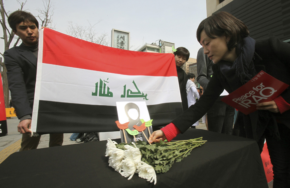 दक्षिण कोरिया में मारे इराकी लोगों को श्रद्धांजलि देती एक महिला।