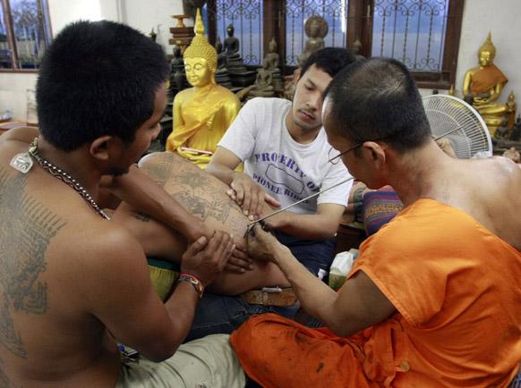 बैंकाक में एक व्यक्ति की पीठ पर टैटू बनाता एक बौद्ध भिक्षु।