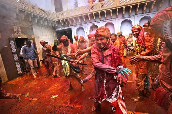 नंदगांव में नंदग्राम मंदिर के प्रांगण में लठ्ठमार होली खेलते लोग।