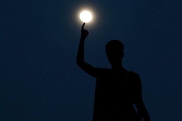 साइप्रस में एक स्टैचू की इस तरह तस्वीर ली गई जैसे लगा रहा है कि चंद्रामा उसकी उंगलियों पर घूम रहा है।