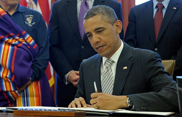 वाशिंगटन हाउस में कानून के कुछ नए प्रावधानों पर हस्ताक्षर करते अमेरिकी राष्ट्रपति बराक ओबामा।