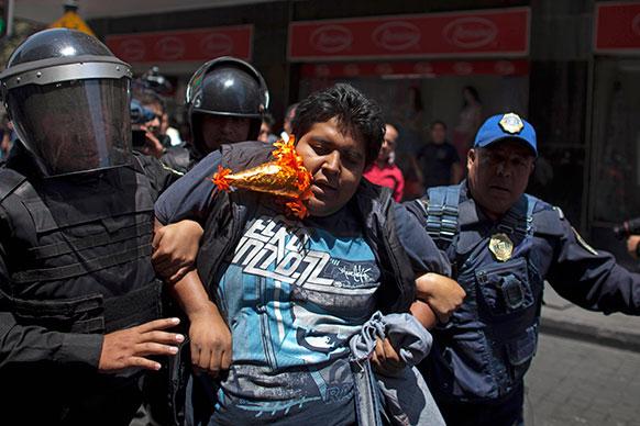 मैक्सिको सिटी में पुलिस और प्रदर्शनकारियों से झड़प के दौरान एक विरोधी को पुलिस ने गिरफ्तार कर लिया।