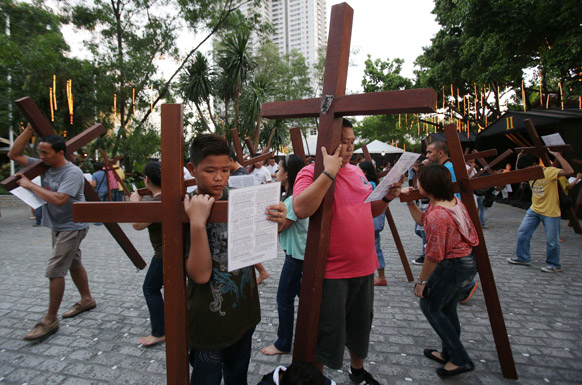 मनीला में कुछ बच्चे इसा मसीह के क्रास के साथ।