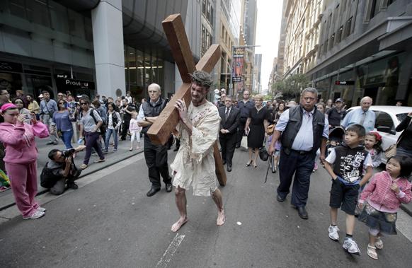 गुड फ्राइडे के मौके पर ऑस्ट्रेलिया का एक दृश्य जिसमें एक व्यक्ति इसा मसीह के रूप में अपने कंधे पर क्रास लेकर चल रहा है।