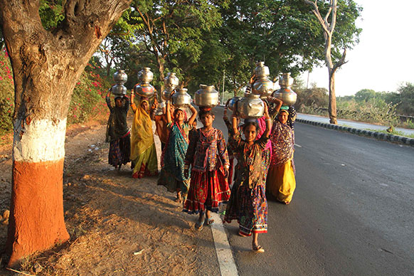 वडोदरा के बाहरी इलाके से पेयजल लेकर लौटतीं महिलाएं।