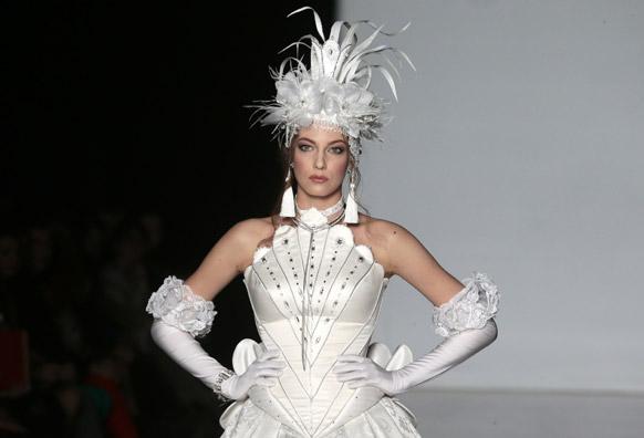 मास्को फैशन वीक के दौरान डिजायनर स्लावा जैतसेव के कपड़ों को पेश करती एक मॉडल।
