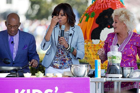 वाशिंगटन के व्हाइट हाउस स्थित साउथ लॉन में ब्रोकली रेबे पास्तो का टेस्ट लेती हुई अमेरिका की प्रथम महिला मिशेल ओबामा।