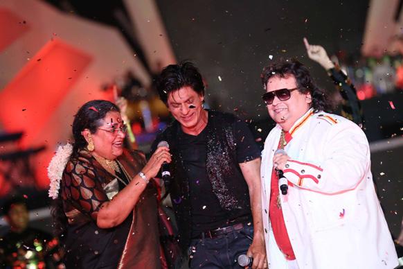 आईपीएल 6 के ओपनिंग सेरेमनी के दौरान प्रसिद्ध गायिका उषा उथ्थप और बप्पी लाहिरी के साथ परफॉरमेंस देते हुए पश्चिम बंगाल के ब्रैंड एंबेसेडर शाहरूख खान। फोटो सौजन्य: रवि शंकर तुलसान/रेड चिलीज एंटरटेनमेंट।