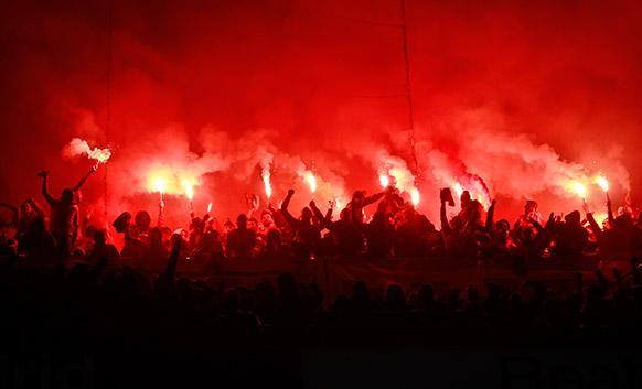 मैड्रिड में एक फुटबाल मैच से पहले मशाल जलाकर जमा हुए लोग।