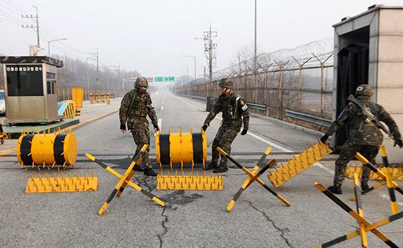 दक्षिण कोरिया में चेकिंग के लिए बैरिकेड्स लगाते पुलिसकर्मी।