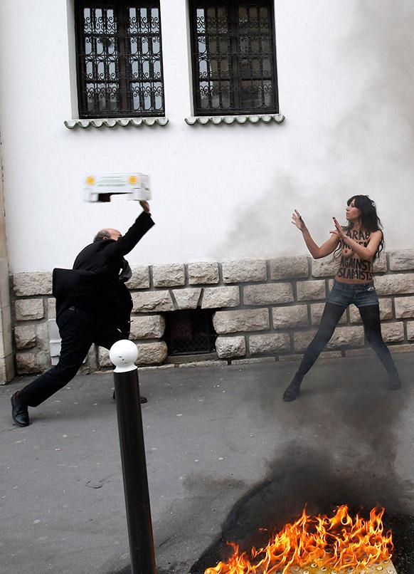 पेरिस में एक प्रदर्शन के दौरान एक व्यक्ति एक महिला पर बॉक्स फेकते हुए।