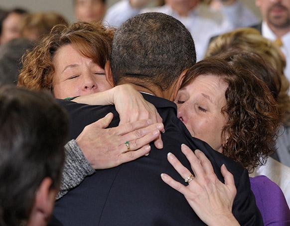 अमेरिकी राष्ट्रपति बराक ओबामा डेनेवर में एक अमेरिकी परिवार को सांत्वना देते हुए।