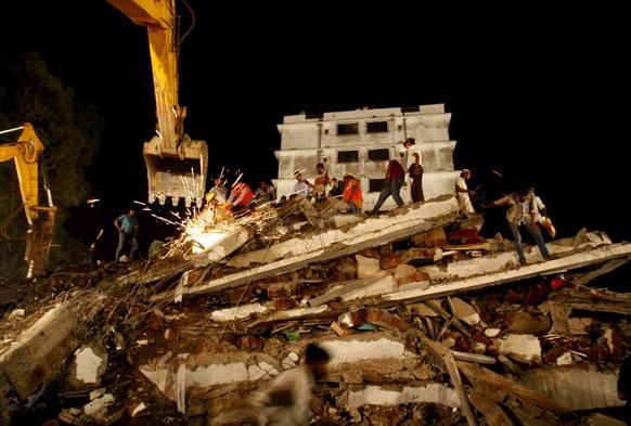 मुंबई के ठाणे में बहुमंजिली इमारत के गिरने के बाद राहत कार्य में जुटे बचाव व राहत दल के कर्मचारी। इस हादसे में अब तक 29 लोगों की मौत हो चुकी है।